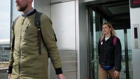El hombre y la mujer con equipaje están saliendo de la elevación al aire libre metrajes