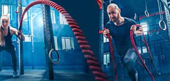 El hombre y la mujer con las cuerdas de la batalla de la cuerda de la batalla ejercitan en el gimnasio de la aptitud foto de archivo libre de regalías