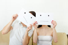 El hombre y la mujer cubren sus caras con sonrisa triste dibujadas en los wi del papel Fotos de archivo libres de regalías