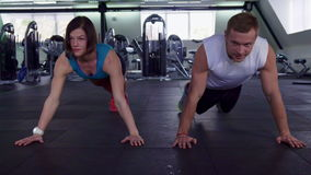 El hombre y la mujer de la aptitud hacen pectorales en el gimnasio metrajes