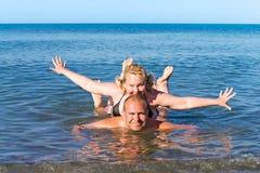 El hombre y la mujer de los años medios juegan el mar como niños Imagen de archivo libre de regalías