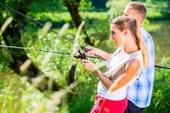 El hombre y la mujer de la pesca así como la barra en el río echan a un lado foto de archivo