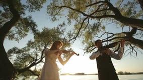 El hombre y la mujer del dúo del violín tocan el violín en la naturaleza en la puesta del sol en el lago almacen de metraje de vídeo
