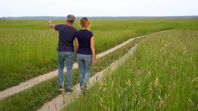 El hombre y la mujer delgados en vaqueros van en el camino forestal en el campo entre alta hierba verde y admiran la naturaleza e metrajes