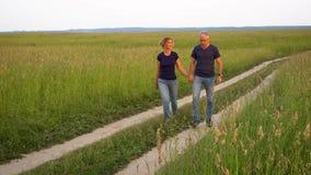 El hombre y la mujer delgados en vaqueros van en el camino forestal en el campo entre alta hierba verde y admiran la naturaleza e almacen de video
