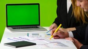 El hombre y la mujer dibujan un gráfico Trabaje con el monitor verde de la pantalla en la oficina almacen de metraje de vídeo