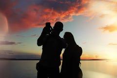 El hombre y la mujer en la puesta del sol hace una foto Fotografía de archivo