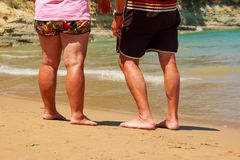 El hombre y la mujer en pantalones cortos que caminan en el mar varan día soleado del verano Vacaciones en el mar tiempo del reti foto de archivo