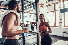 El hombre y la mujer están hablando durante rotura en gimnasio fotos de archivo libres de regalías