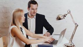 El hombre y la mujer están mirando el ordenador en la oficina