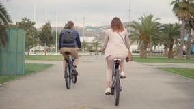 El hombre y la mujer están montando las bicis en parque de la ciudad en día nublado en el verano, opinión de la parte posterior metrajes