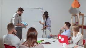 El hombre y la mujer están presentando a los compañeros de trabajo su informe en el encuentro, metrajes
