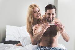 El hombre y la mujer felices están contando con al bebé Imágenes de archivo libres de regalías