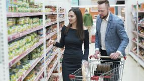 El hombre y la mujer felices jovenes eligen productos en tienda almacen de metraje de vídeo