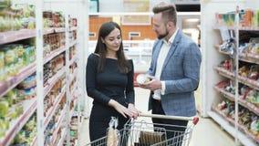 El hombre y la mujer felices jovenes eligen productos en tienda metrajes