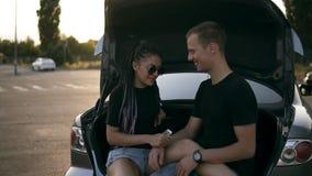 El hombre y la mujer felices jovenes se están sentando juntos en el tronco de coche abierto Sonriendo, los pares alegres se acari almacen de metraje de vídeo
