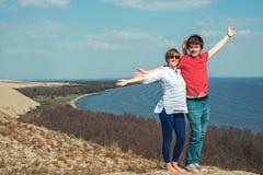 El hombre y la mujer felices se están colocando en la montaña Foto de archivo