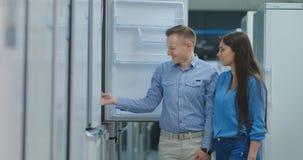 El hombre y la mujer jovenes de los pares eligen el nuevo refrigerador almacen de video