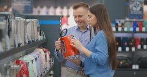El hombre y la mujer jovenes de los pares en tienda de dispositivos elige una caldera eléctrica en el contador metrajes