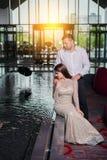 El hombre y la mujer junta miran el agua en la piscina donde la nadada de los pescados imagenes de archivo