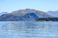 El hombre y la mujer kayaking en el lago natural hermoso en el verano calientan la estación, rodeada con las montañas y el fondo  Fotos de archivo libres de regalías