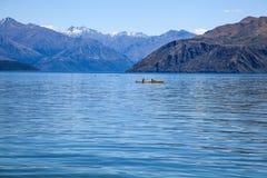 El hombre y la mujer kayaking en el lago natural hermoso en el verano calientan la estación, rodeada con las montañas y el fondo  Foto de archivo libre de regalías