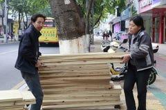 El hombre y la mujer llevan el tablón de la madera fotos de archivo