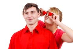 El hombre y la mujer loca lleva a cabo corazones rojos sobre ojos Imágenes de archivo libres de regalías