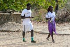 El hombre y la mujer locales no identificados en uniforme del fútbol caminan después fotografía de archivo