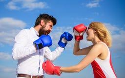El hombre y la mujer luchan el fondo del cielo azul de los guantes de boxeo Defienda su opinión en la confrontación Pares en la l fotografía de archivo libre de regalías