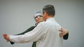 El hombre y la mujer mayores de los pares está bailando un vals en un fondo blanco almacen de video