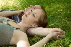 El hombre y la mujer mienten en una hierba Foto de archivo