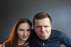 El hombre y la mujer miran adelante con la cólera y la duda, caras del ceño fruncido fotos de archivo