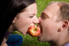 El hombre y la mujer muerden una manzana roja Imágenes de archivo libres de regalías