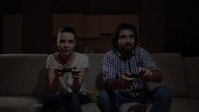El hombre y la mujer platying el juego Utilizan la palanca de mando La muchacha se inclina a los left and right El individuo hace metrajes