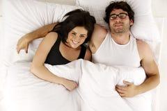 El hombre y la mujer pusieron en la cama blanca que consideraba para arriba la sonrisa de la cámara Imagen de archivo libre de regalías