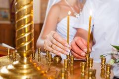 El hombre y la mujer pusieron una vela en iglesia fotos de archivo libres de regalías