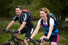 El hombre y la mujer que gozan de una bici montan en naturaleza Imagen de archivo libre de regalías