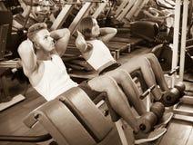 El hombre y la mujer que hacen el ABS ejercitan en gimnasio Fotografía de archivo