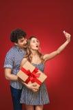 El hombre y la mujer que hacen el selfie llaman por teléfono a Pin Up con un regalo en estilo, es Imagen de archivo