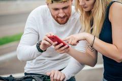 El hombre y la mujer que miran el teléfono descubren la ruta Imagen de archivo libre de regalías
