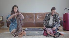El hombre y la mujer que se sientan en el piso en casa delante de un sof? de cuero, embalando una maleta antes de viaje El marido almacen de metraje de vídeo
