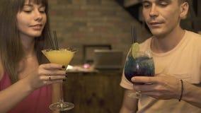 El hombre y la mujer que se sostienen en manos beben de largo los vidrios del cóctel y del tintineo en la igualación del restaura almacen de metraje de vídeo