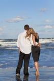 El hombre y la mujer románticos juntan el abarcamiento en una playa Imágenes de archivo libres de regalías