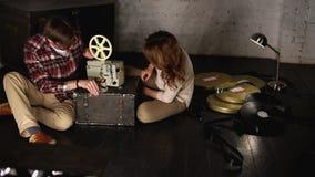 El hombre y la mujer sacan el proyector almacen de metraje de vídeo