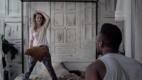 El hombre y la mujer se divierten en la mañana Los pares multirraciales en pijamas tienen lucha al lado de las almohadas Tiempo d almacen de metraje de vídeo