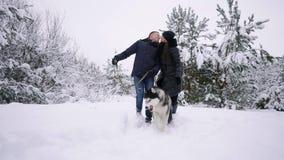 El hombre y la mujer se divierten que caminan con el husky siberiano en nieve que juega y que lanza del bosque del invierno en la almacen de video