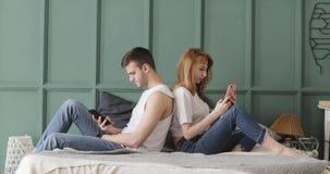 El hombre y la mujer se están sentando se apoya en cama y la ojeada de sus teléfonos móviles almacen de metraje de vídeo