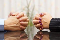 El hombre y la mujer se sienta en un escritorio con las manos abrochadas problema marital Fotografía de archivo libre de regalías