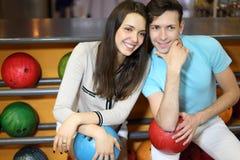 El hombre y la mujer se sientan cerca de estantes en club del bowling Foto de archivo libre de regalías
